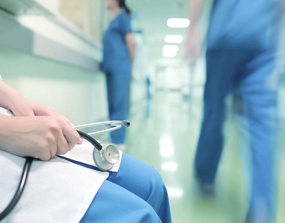 Médico aguardando sentado em corredor de hospital.