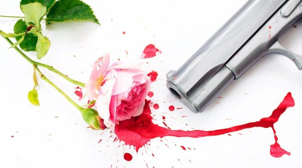 Rosa, sangue rosa e arma de fogo em superfície branca.