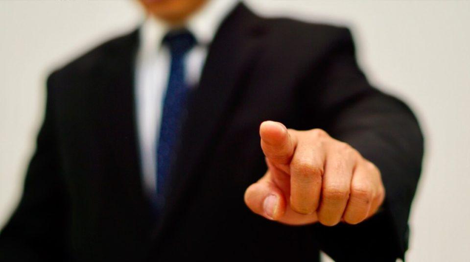 Executivo apontando o dedo indicador.