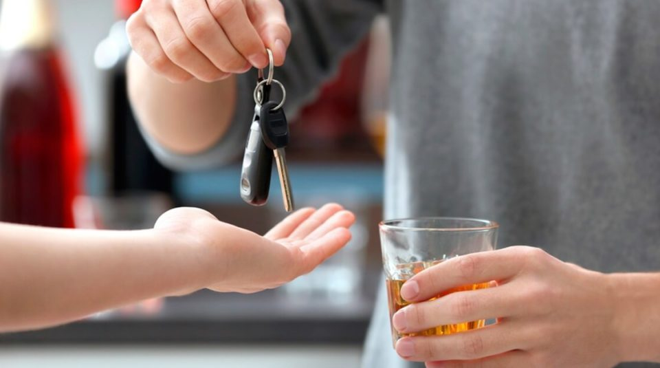 Motorista com copo de cerveja na mão, entregando a chave do veículo para outro condutor.