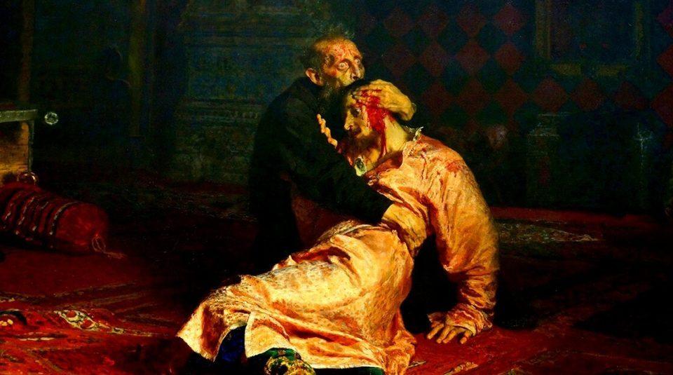 Homem ajoelhado no chão, segurando o corpo de um homem ferido.