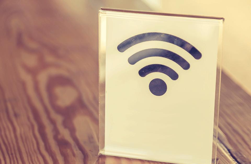 Símbolo de WiFi em placa de acrílico sobre a mesa.