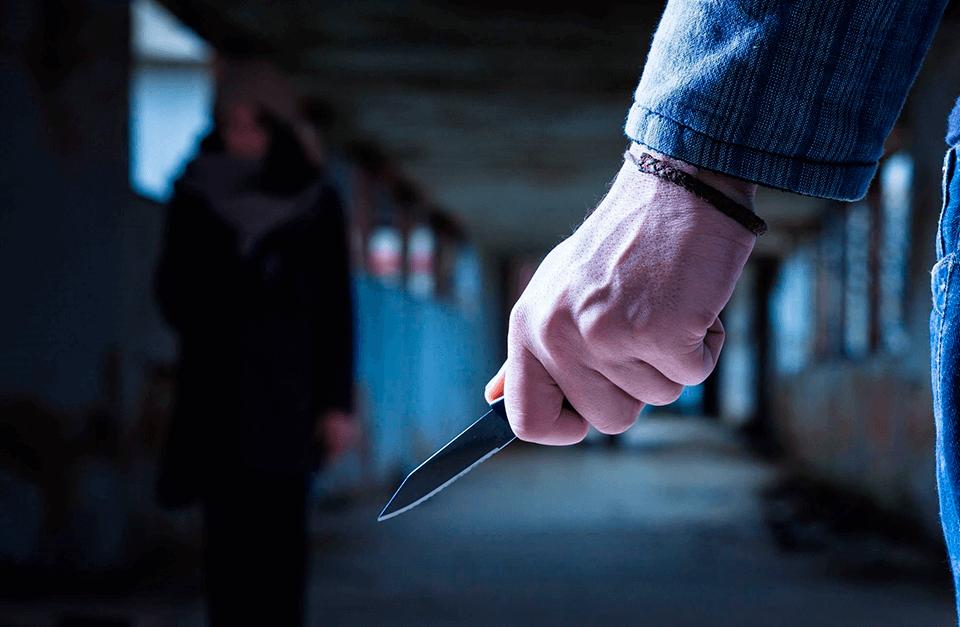 Homem com faca na mão à espera da vítima que caminha por perto.