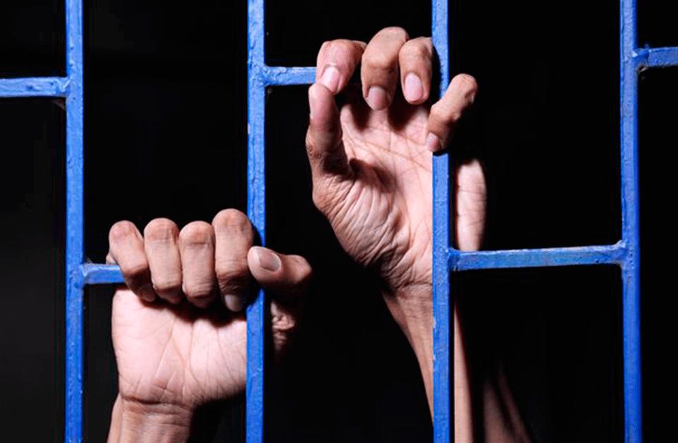 Prisioneiro com as mãos na grade da janela.