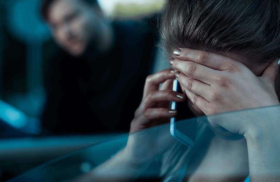 Mulher no carro, ao telefone, com homem a perseguindo.
