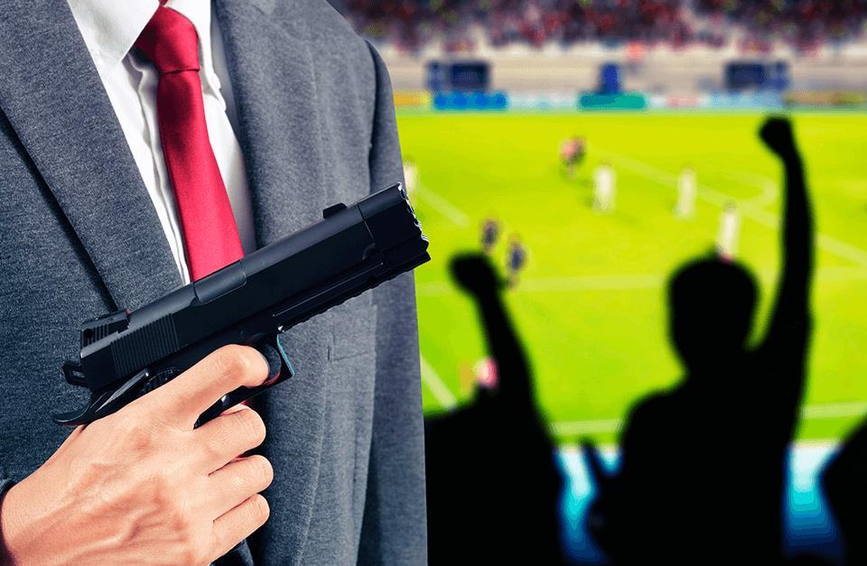 Homem trajado de terno com arma na mão na arquibanca de um estádio de futebol.
