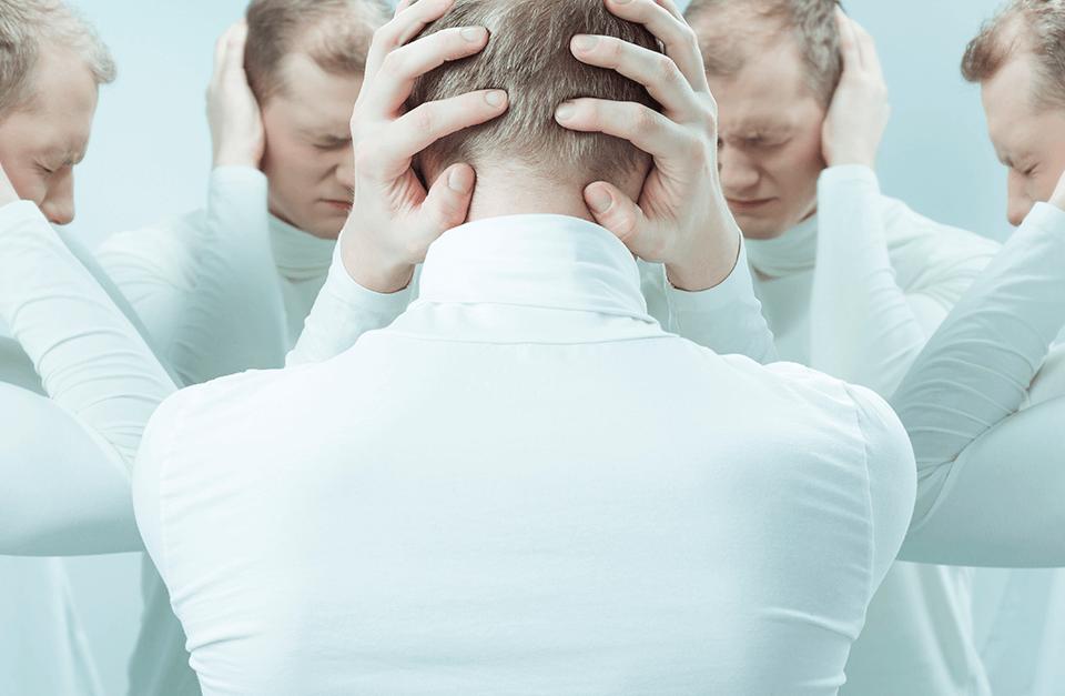 Homens de branco com mãos na cabeça e olhos fechados.