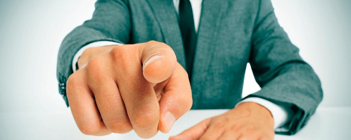 Homem de terno apontando o dedo à câmera.