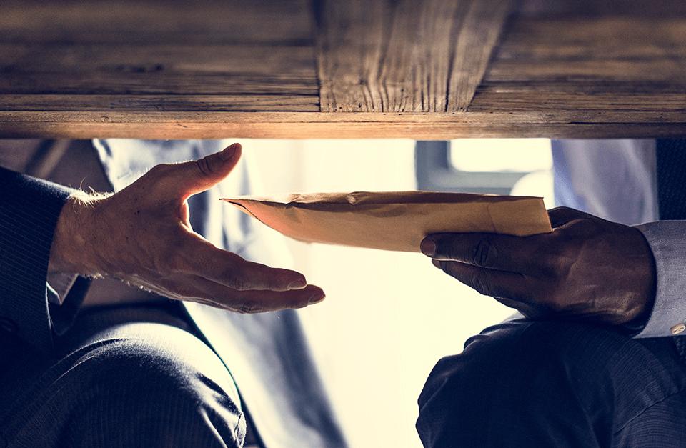 Homens de terno passando envelope pardo por baixo da mesa.