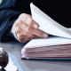 Juiz folheando pilha de papéis sobre a mesa.
